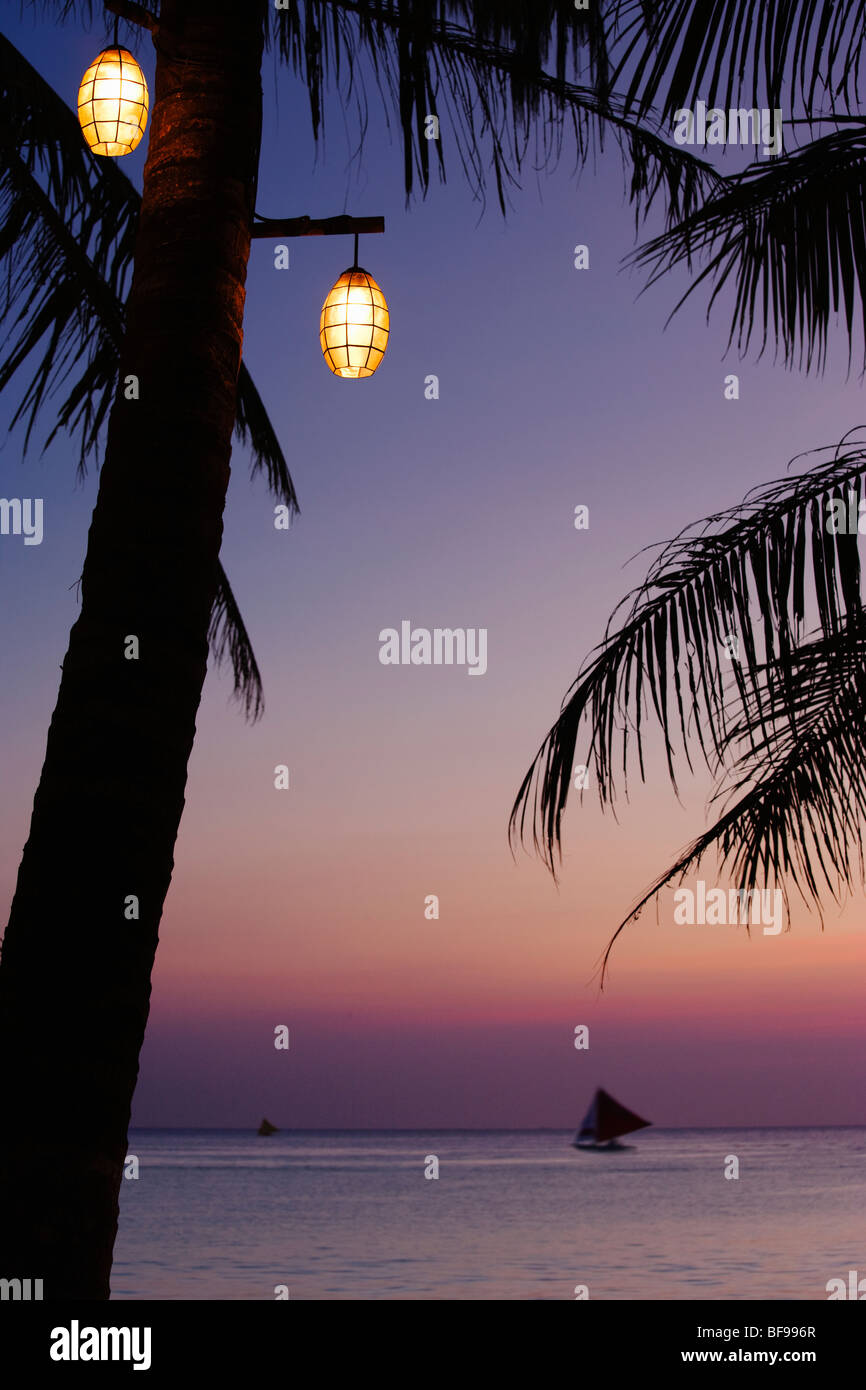 Light in palm tree at dusk and sail boat at sea Boracay; The Visayas; Philippines - Stock Image