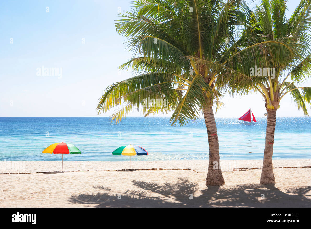 Beach, palms, umbrellas, sea, sand and sail boat in Boracay; The Visayas; Philippines. - Stock Image