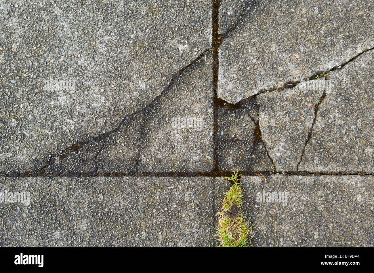 Cracks in the surface of a concrete street. - Stock Image
