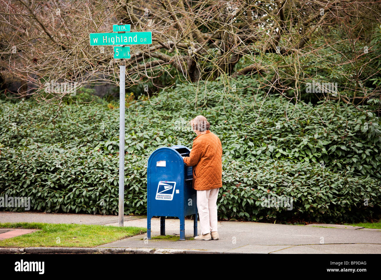 Woman mailing letter at neighborhood mailbox, Highland Drive, Queen Anne, Seattle, Washington - Stock Image