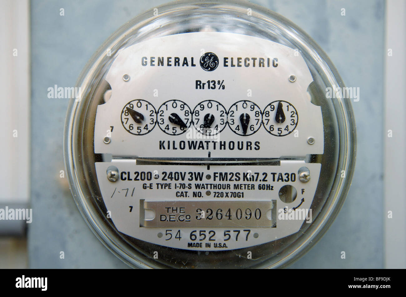 An electric meter tells a utility company how much electricity a home is using. The dials are read left-to-right - Stock Image