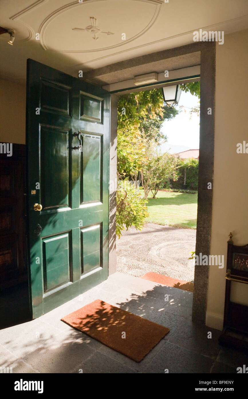 A green open door opening onto a garden on a sunny day Stock Photo