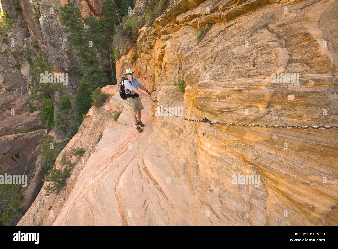 Hiker using chains for support along sheer cliff on Hidden Canyon Trail above Zion Canyon at Zion National Park, - Stock Image