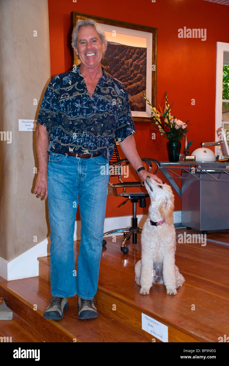Artist Doug West and his dog invite potential customers into his gallery in Arroyo Seco, just north of Taos, New - Stock Image
