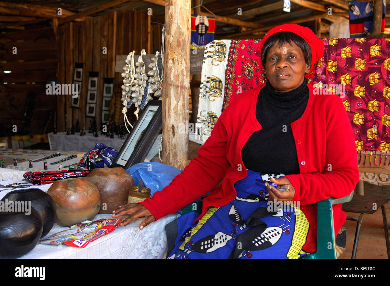 African woman sitting in her curio market stall, Ezulwini, Swaziland - Stock Image