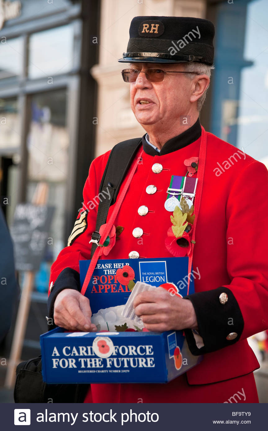 Old soldier collecting for the Royal British Legion poppy appeal in Hereford City UK. Ex-serviceman red uniform - Stock Image