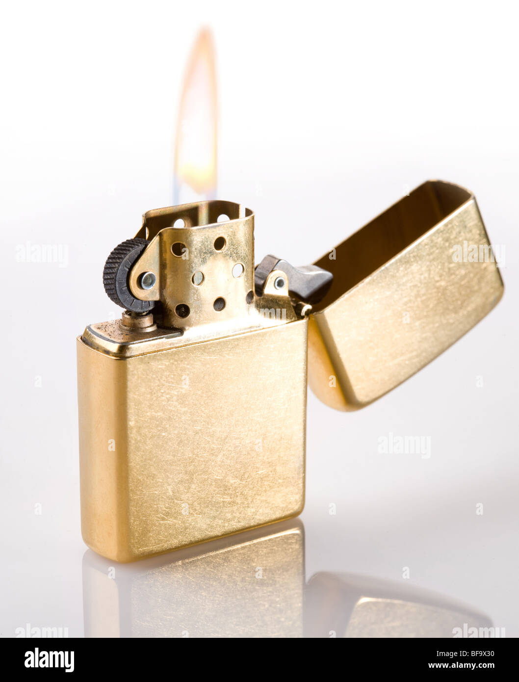 Flaming golden lighter on a white background - Stock Image