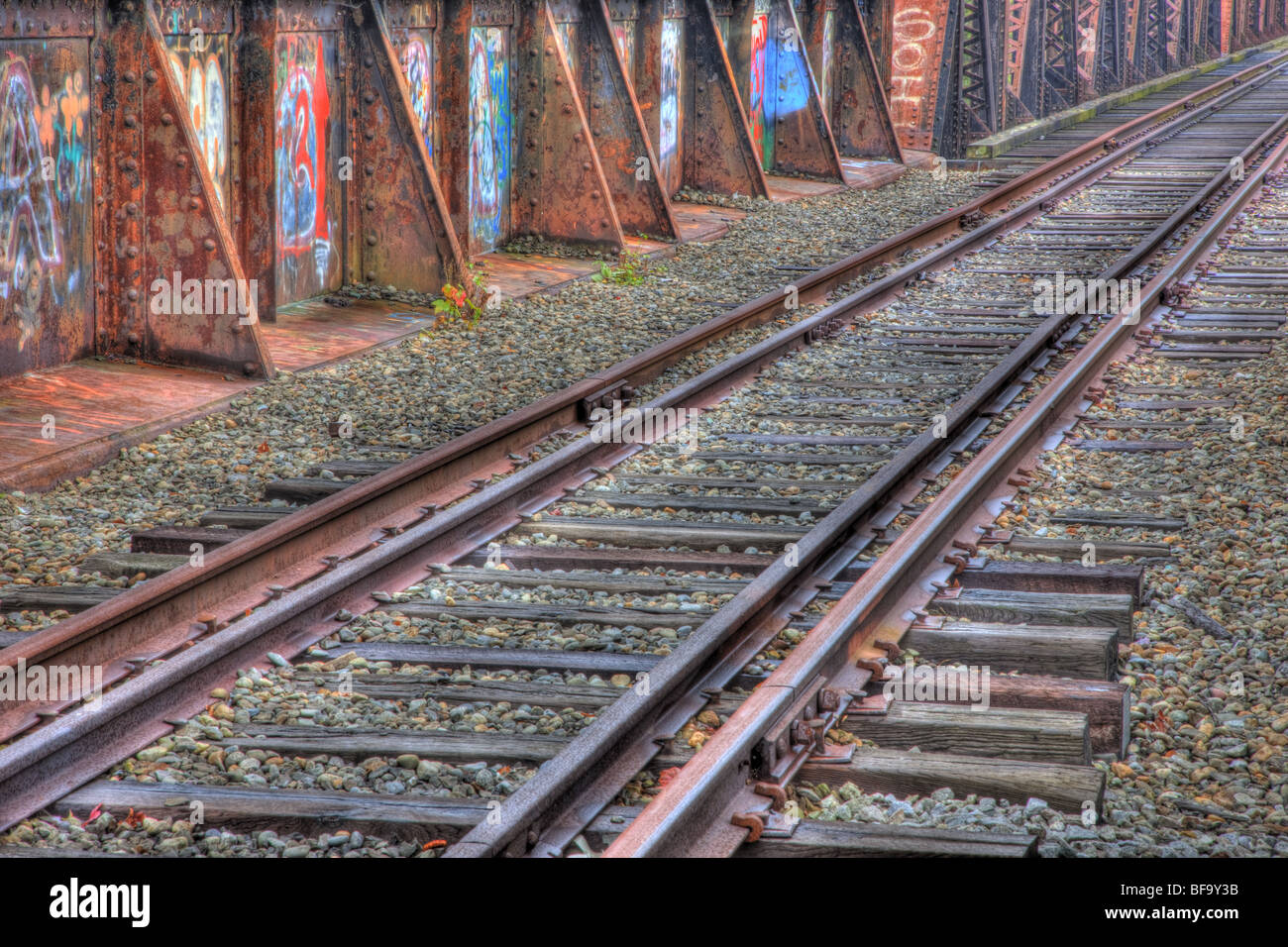 Railroad tracks and graffiti covered deck leading to the historic Free Black Bridge from Brunswick to Topsham, Maine - Stock Image