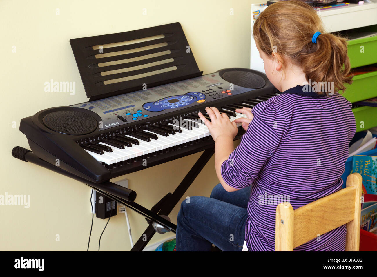 young girl playing Casio synthesizer keyboard - Stock Image