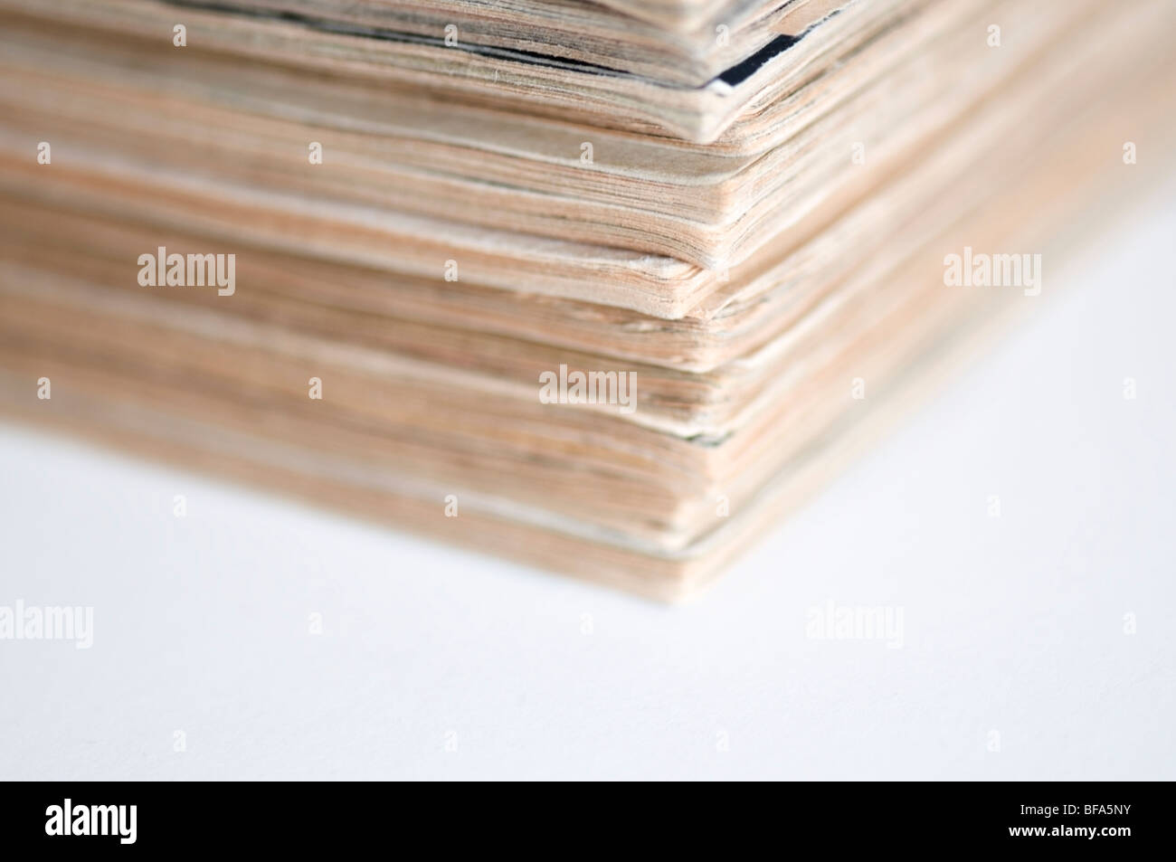 Corner view of piled old, aged, 1960s yellowing magazines copies on white background - Stock Image