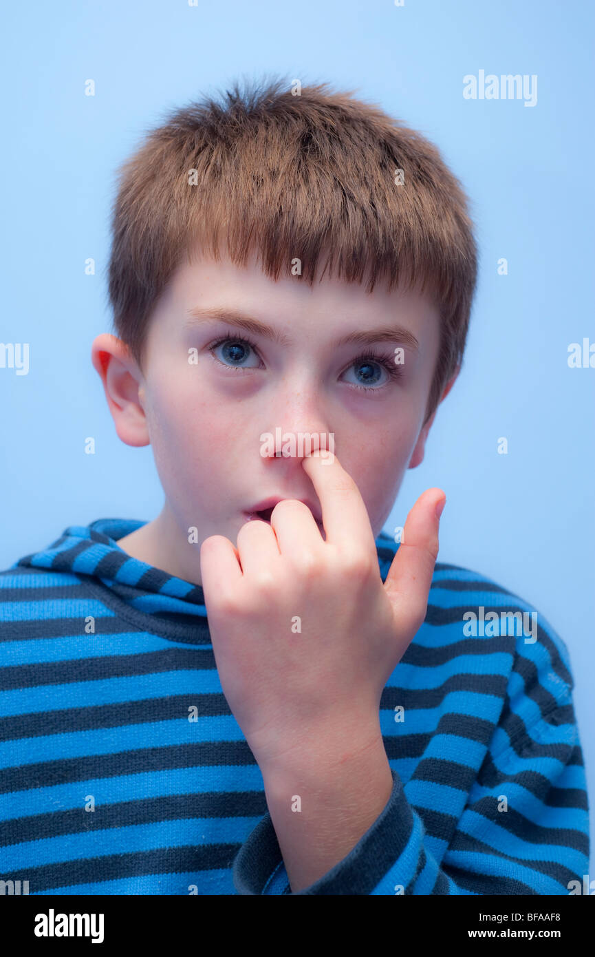 a model released picture of a ten year old boy picking his nose in