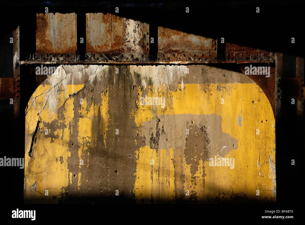 Yellow wall underneath railway viaduct - Stock Image