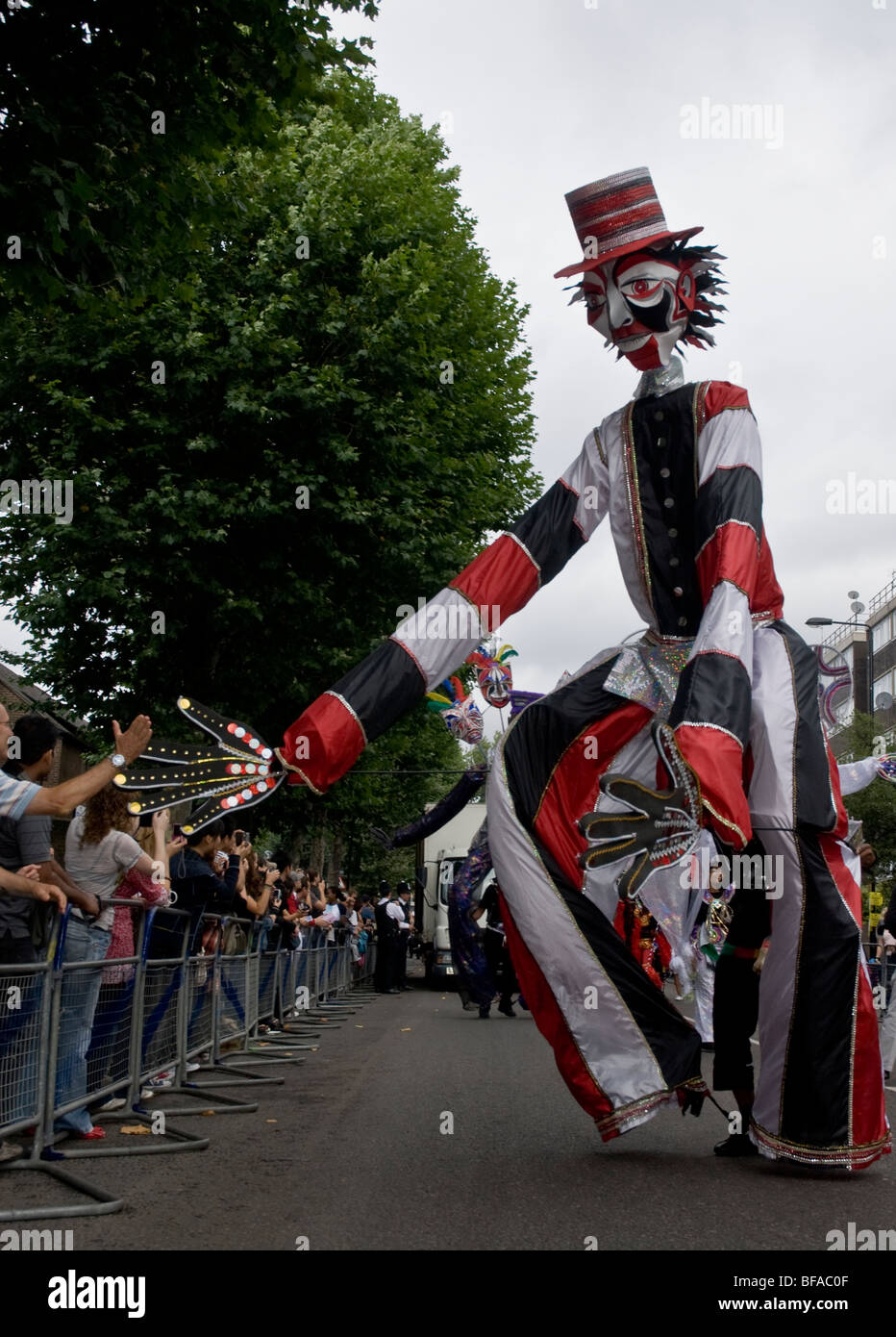 A tall man costume from the Sunshine International Arts float at the Notting Hill carnival in London & A tall man costume from the Sunshine International Arts float at the ...