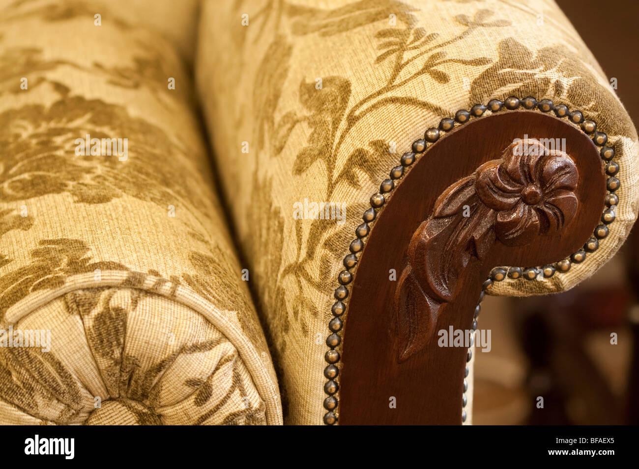 Hard carved armrest on upholstered couch. - Stock Image