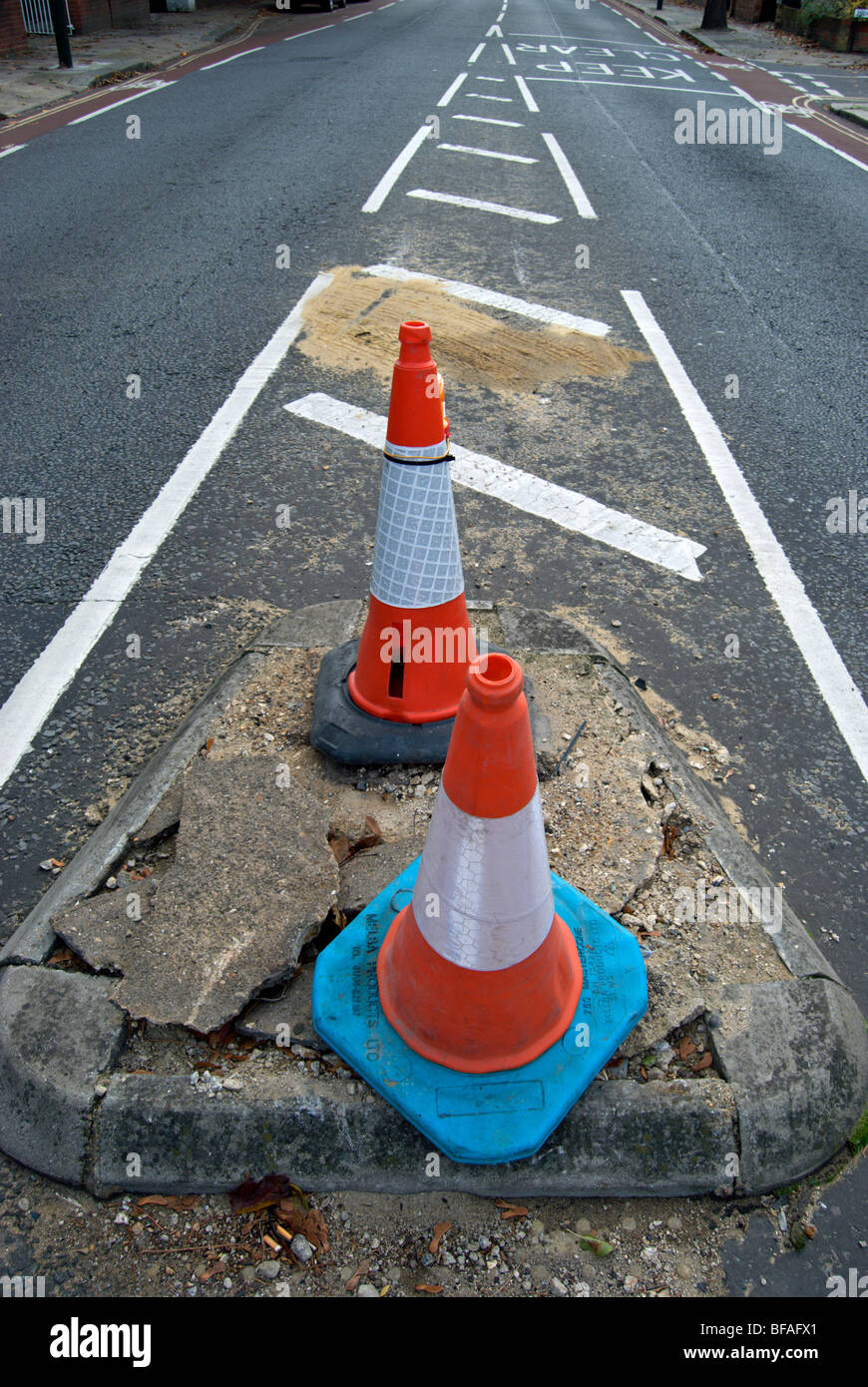 two traffic cones marking a damaged section of road in teddington, middlesex, england - Stock Image
