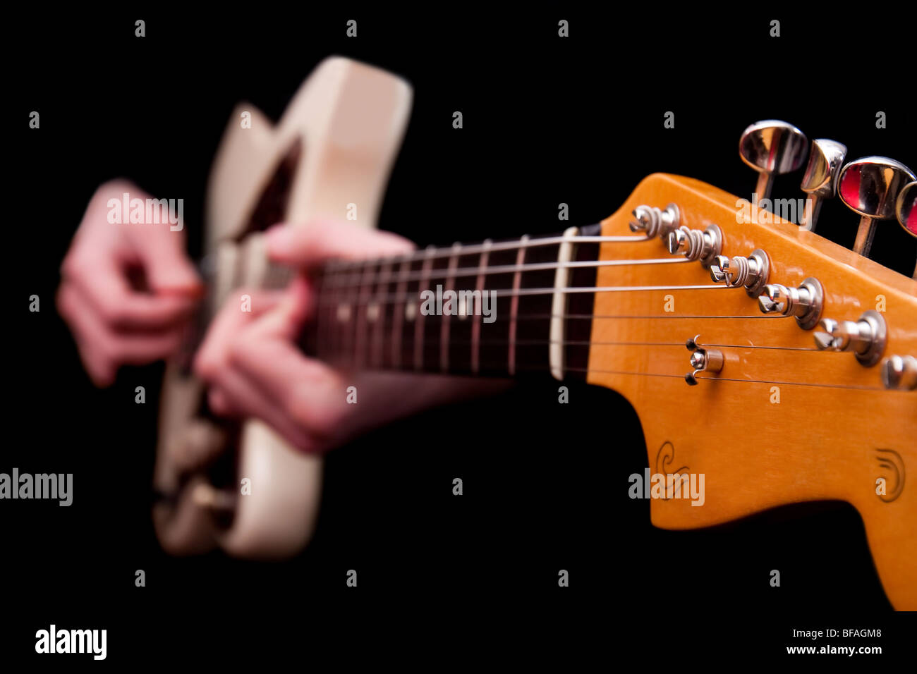 Acoustic electric jazz guitar with blurred hands being played, isolated on black. - Stock Image