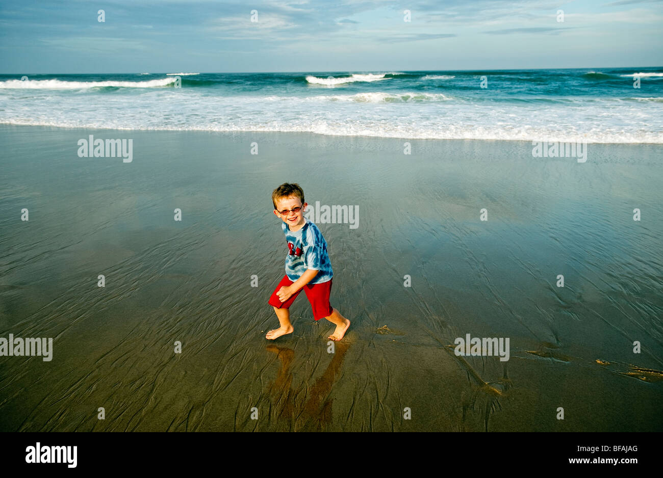 Boy playing at the beach. - Stock Image