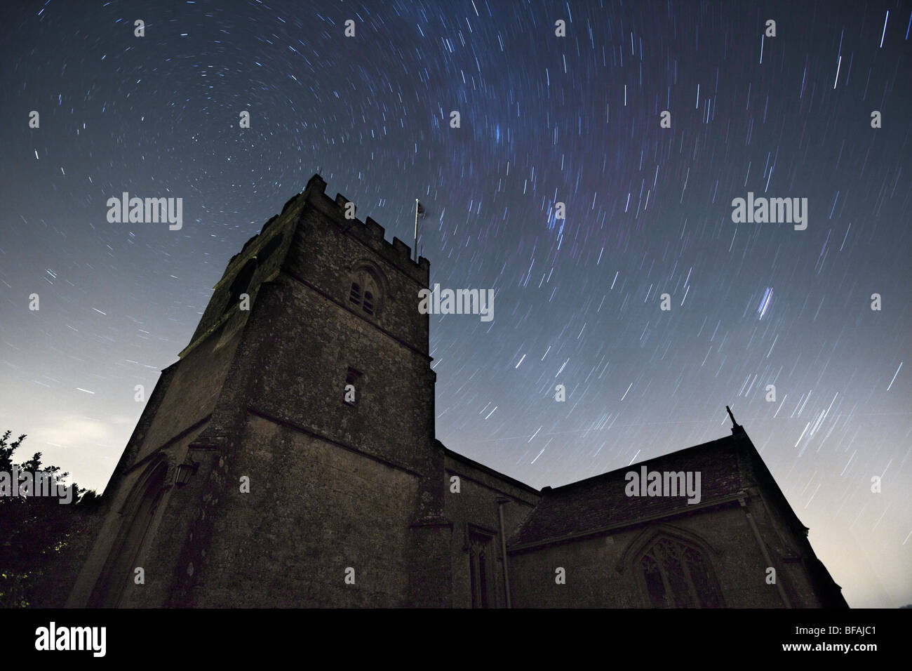 St.Michael's church at Guiting Power in the Cotswolds and star trails. - Stock Image