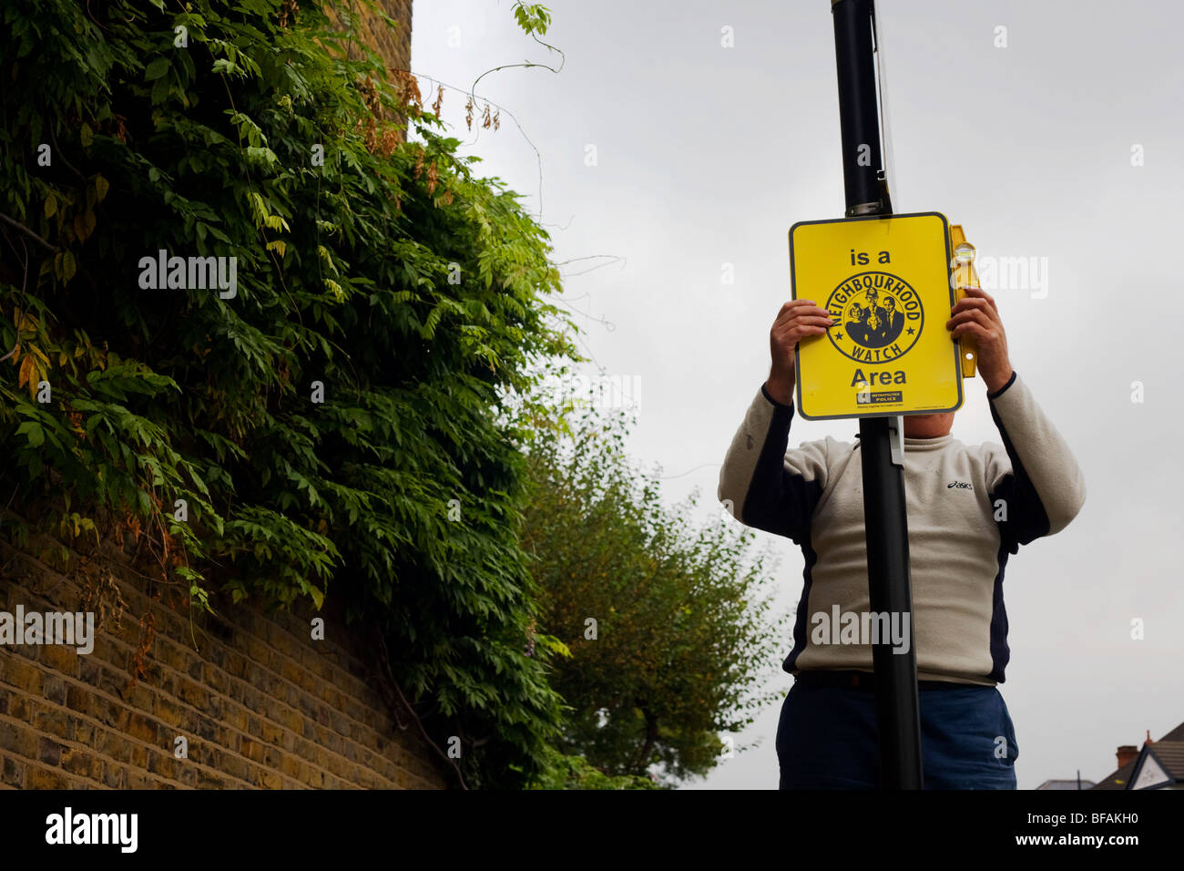 A Lambeth council employee hangs a new Neighbourhood Watch sign on a Lambeth borough lamp post in London. - Stock Image