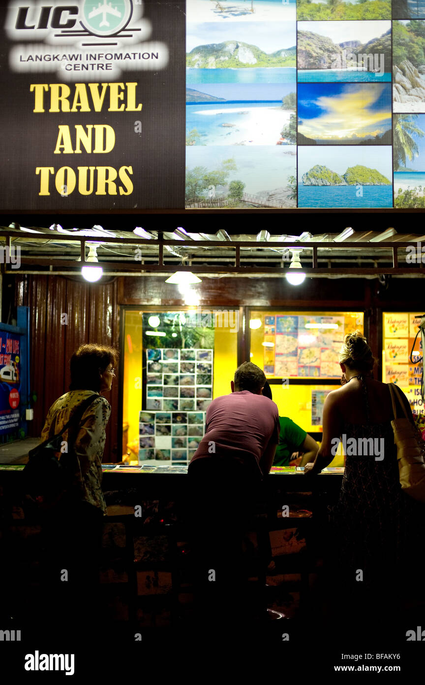 Tourists at an information centre in Pantai Cenang in Langkawi Malaysia.  Photo by Gordon Scammell - Stock Image