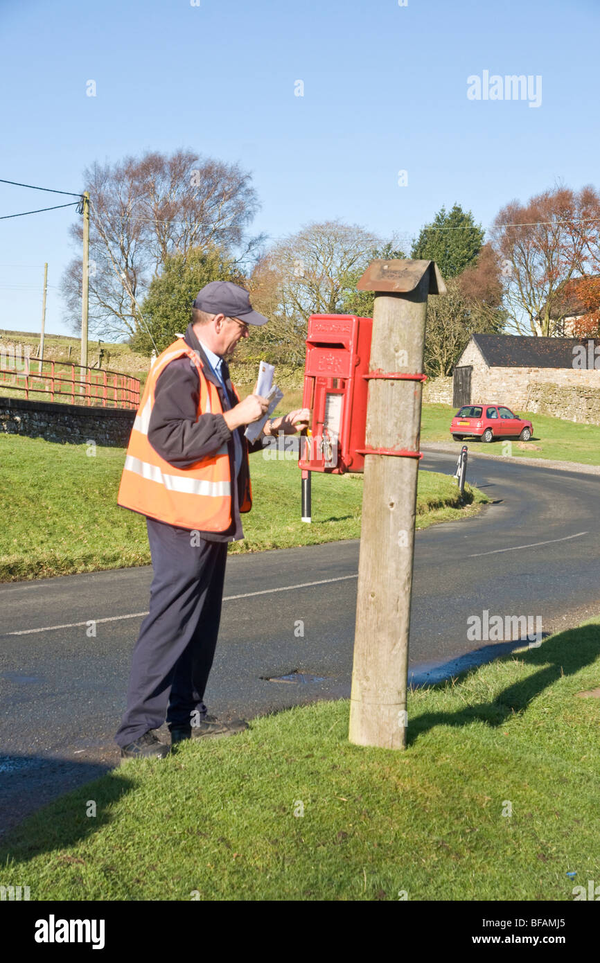 Postman collecting letters from a rural post box near Reeth, Swaledale. - Stock Image