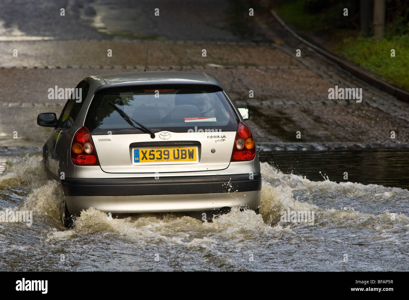 Motor vehicles driving through a flooded weir - Stock Image