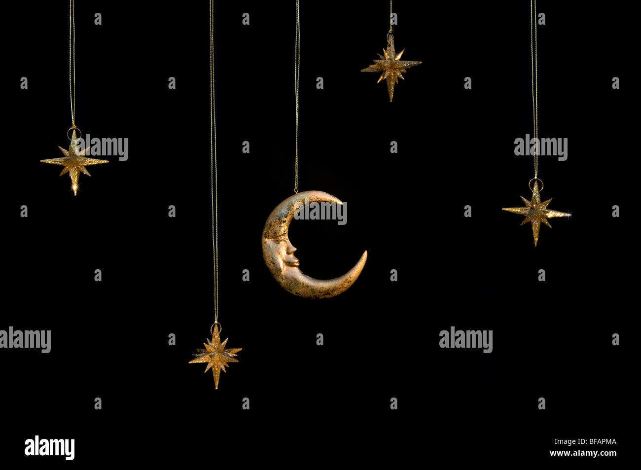Gold shiny moon and stars sparkly hanging christmas decorations against a black background Stock Photo