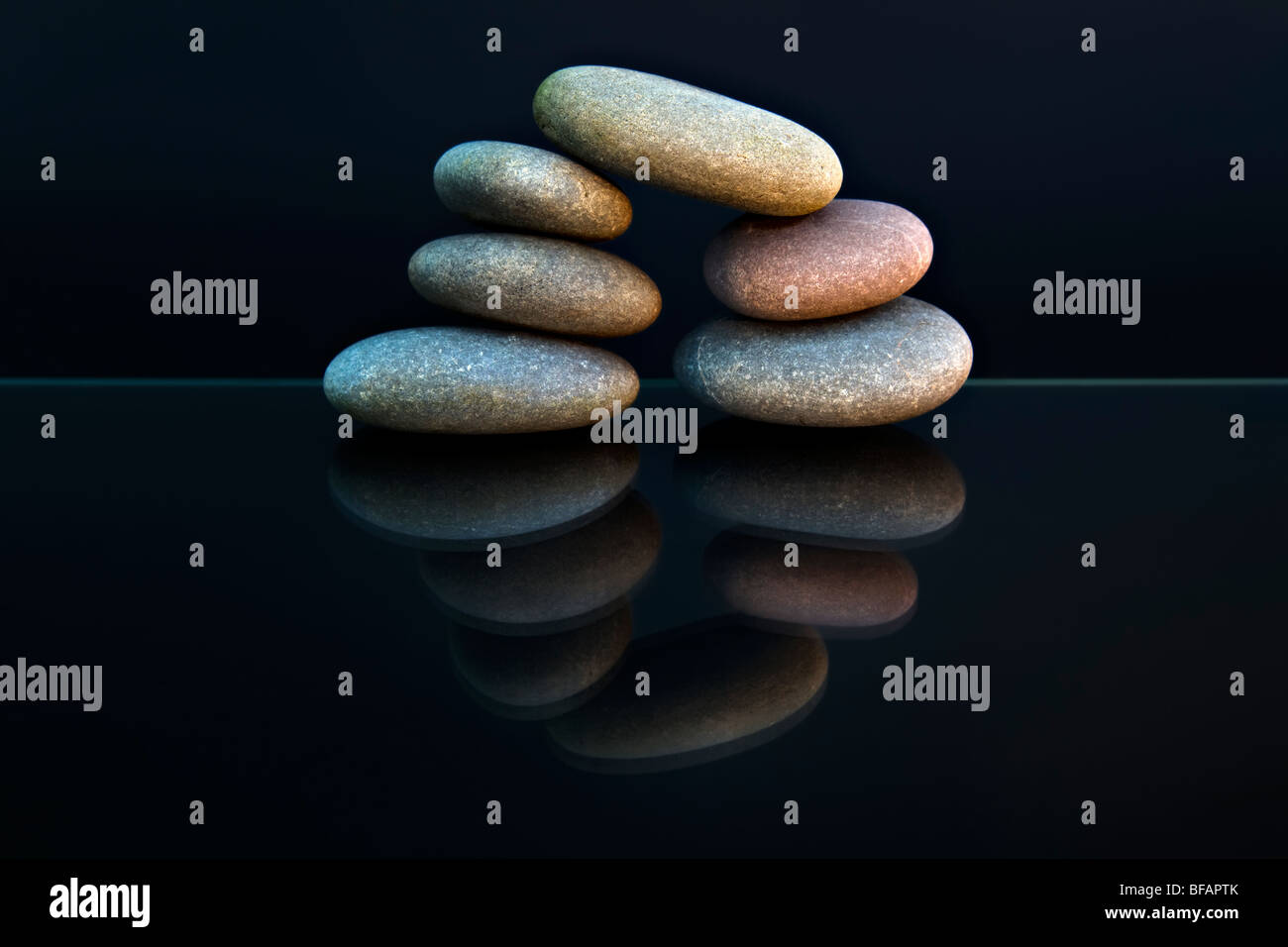 Still life shot of beach pebbles balanced in a stone pile against black background with reflection making a circular - Stock Image