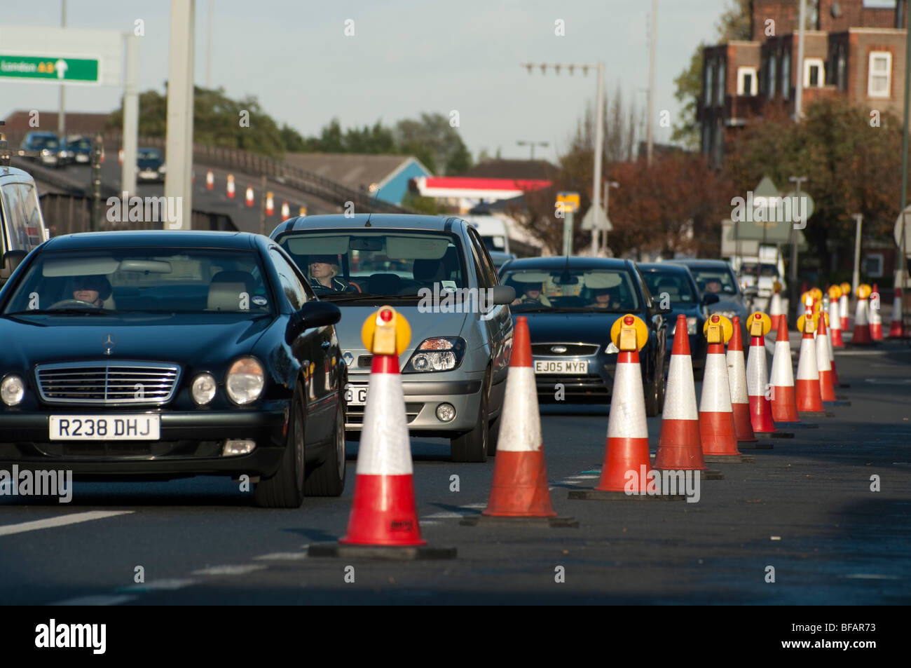 cars pass road works and traffic cones - Stock Image