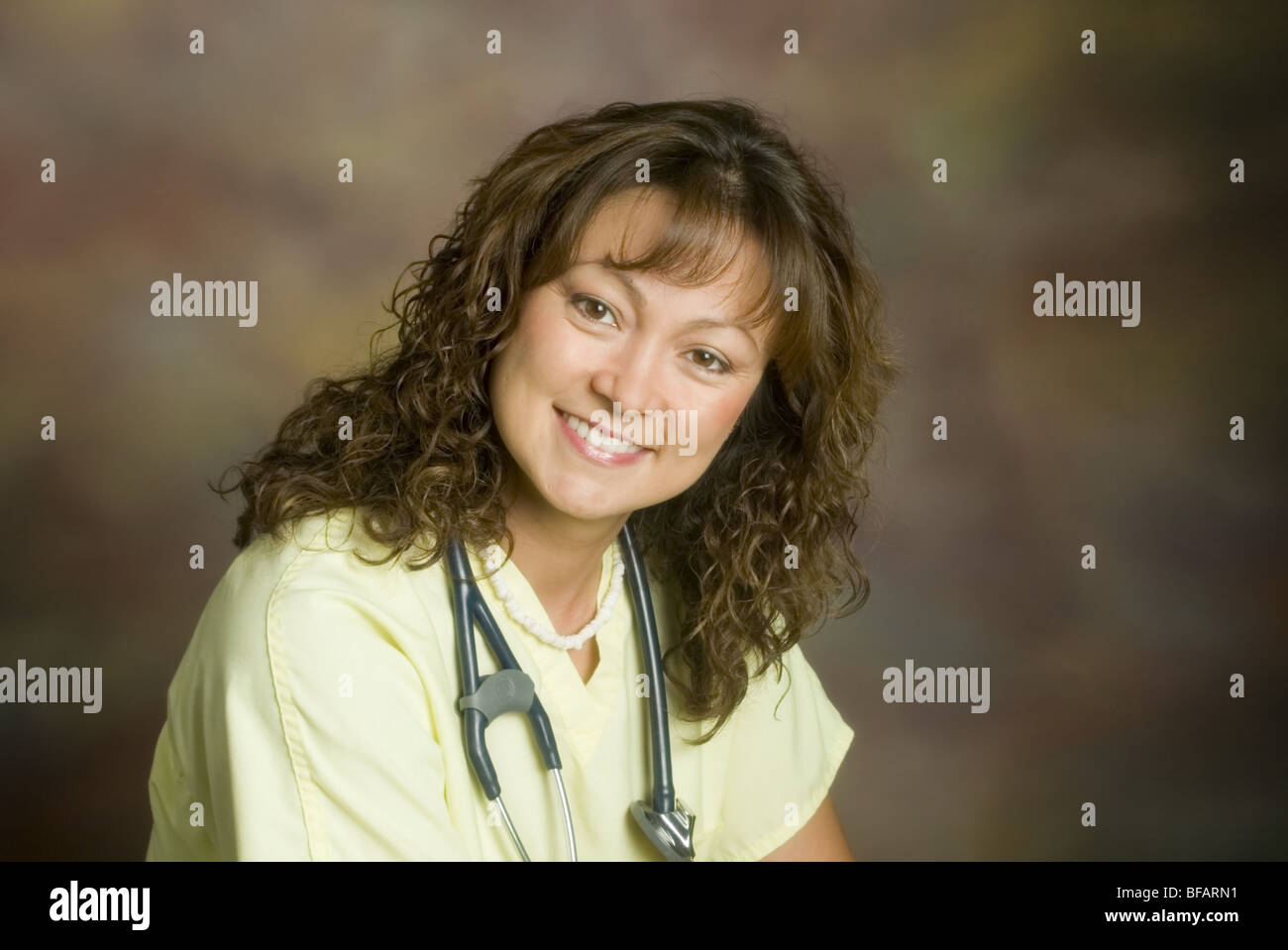 Young nurse studio background, portrait, direct to camera - Stock Image