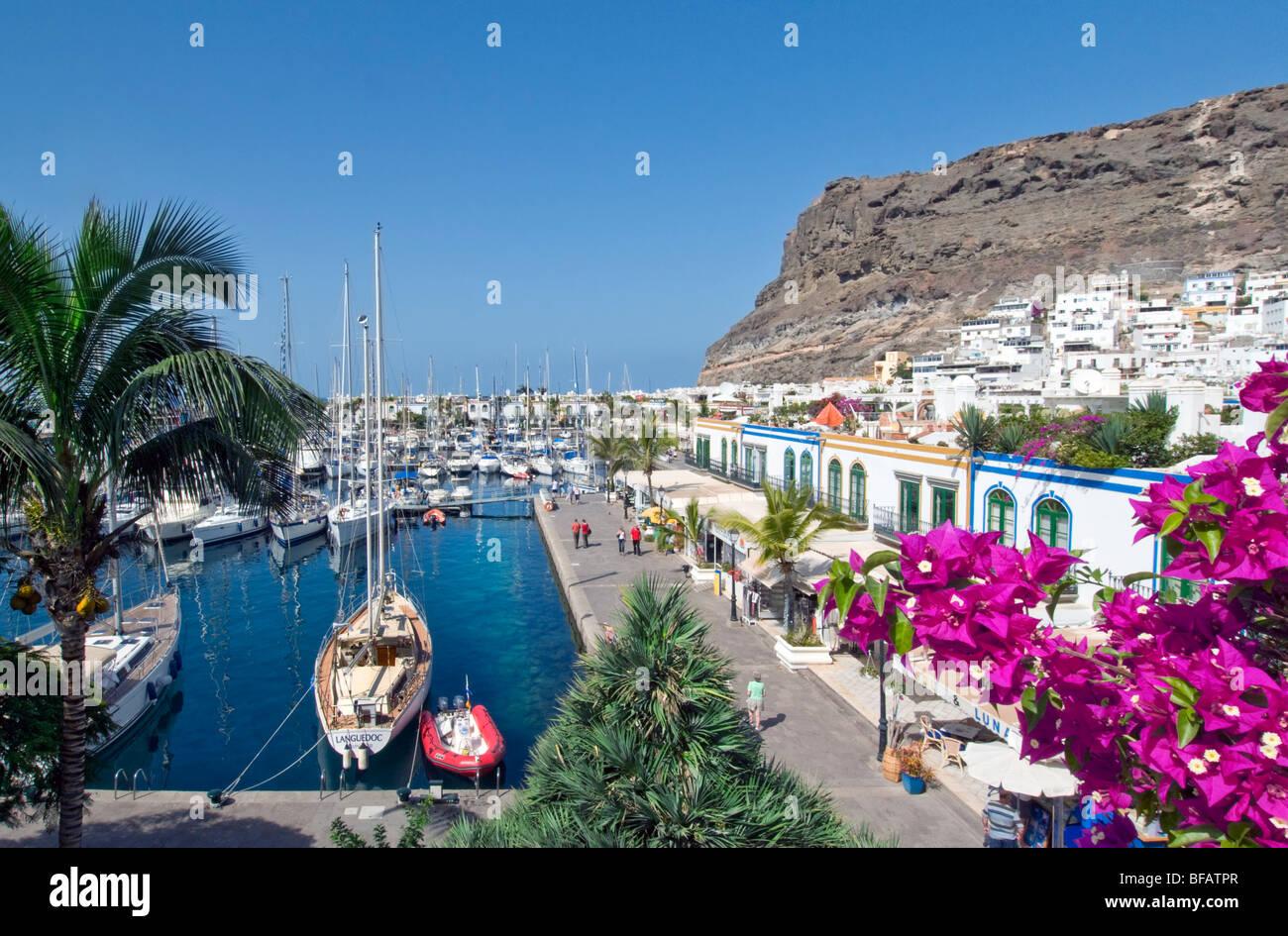 Puerto de Mogan view over bougainvillea flowers to yacht marina  promenade and restaurants  Gran Canaria Canary - Stock Image