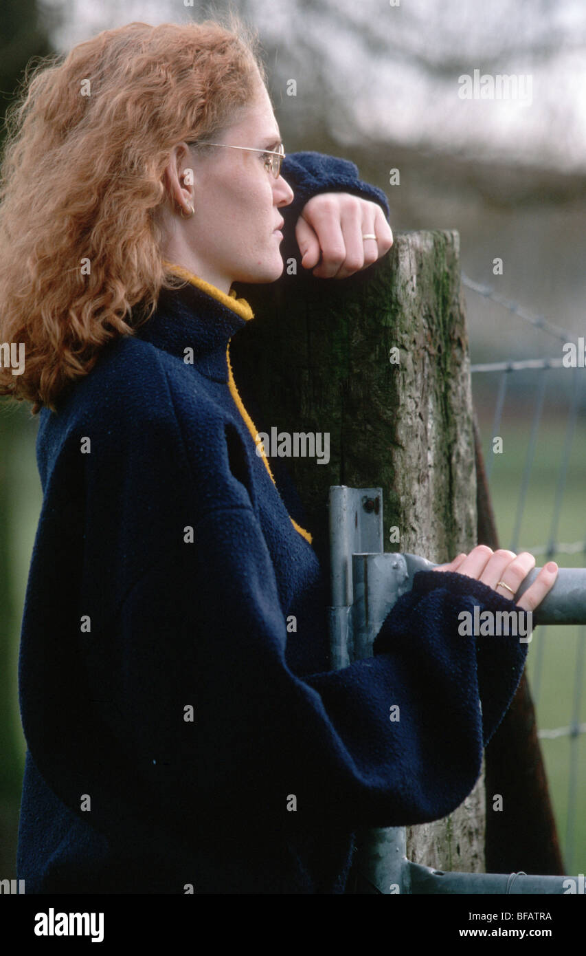 Woman leaning on a fence, one only - Stock Image