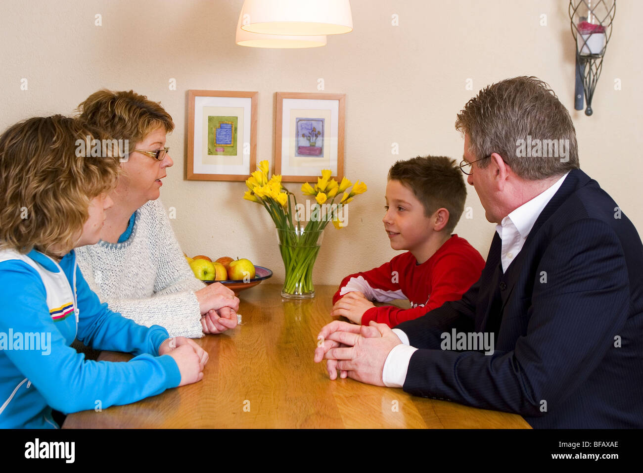 Parents with two children having a family meeting - Stock Image
