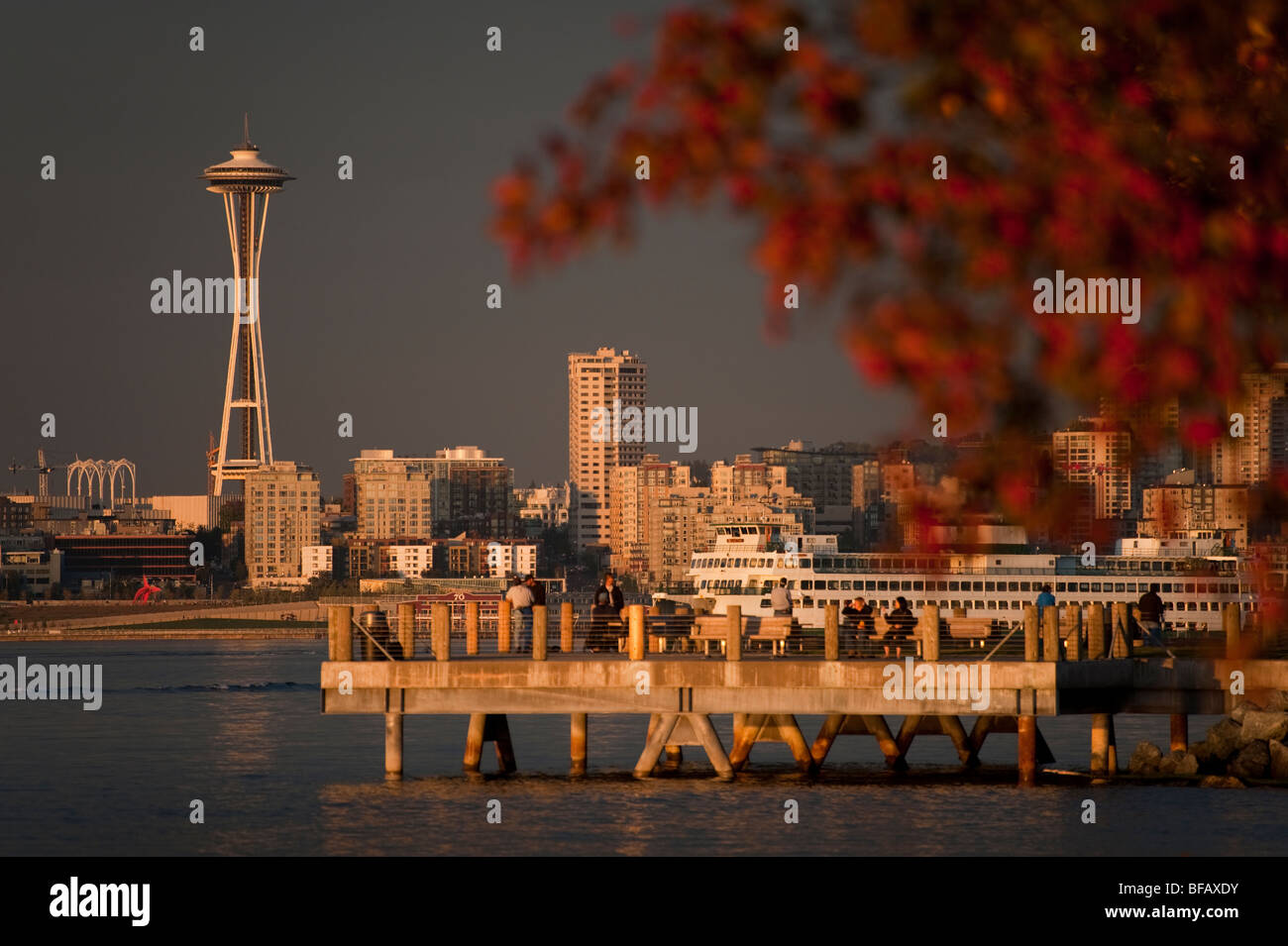 A beautiful autumn sunset from an Alki Beach public pier with the Space Needle and ferry boats going by on Elliott - Stock Image