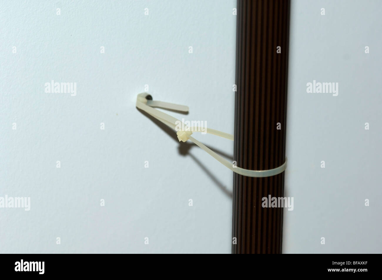 A lamp post secured to a wall using a screw and zip-ties for baby safety and home childproofing. - Stock Image