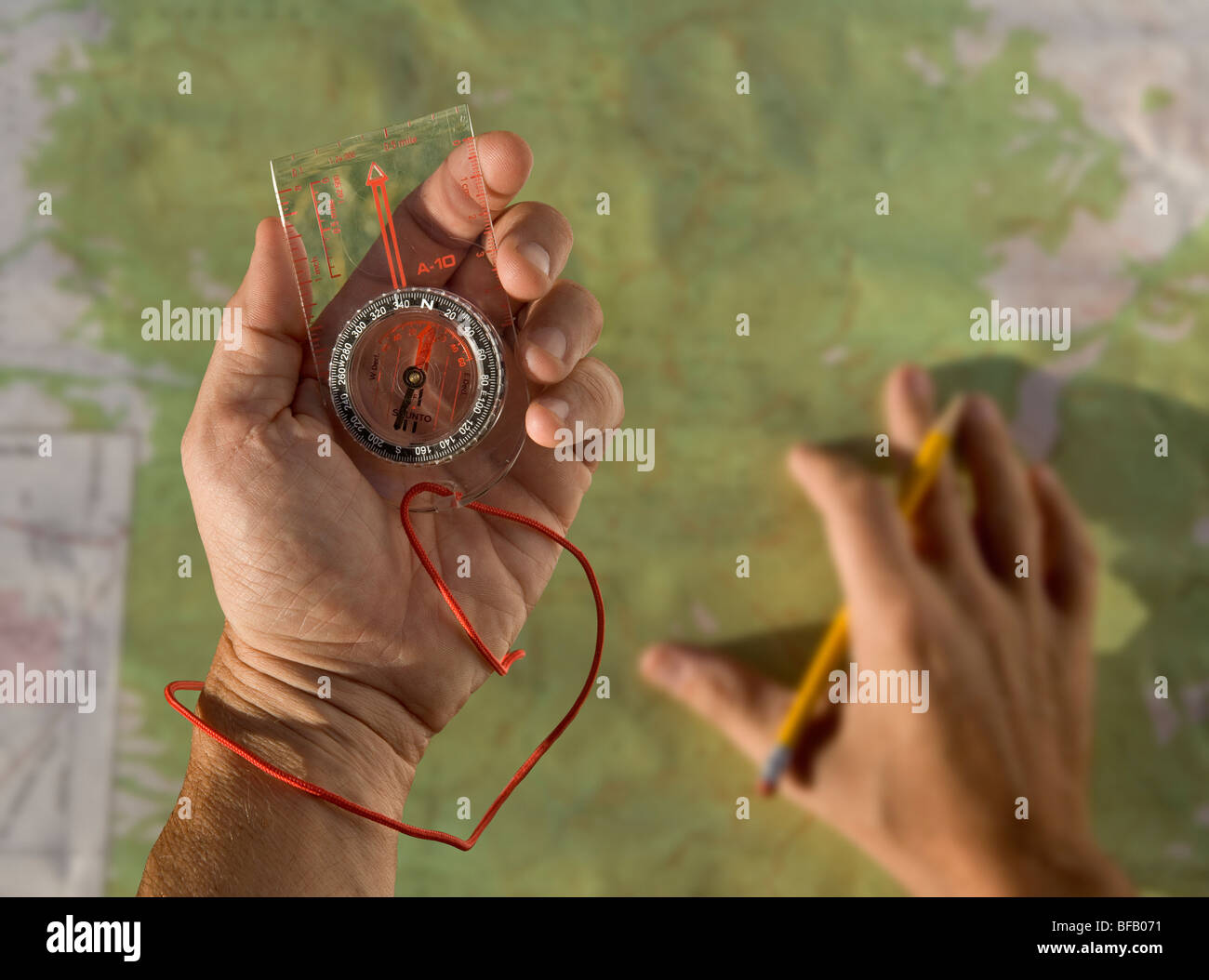 A person using a compass and topo map while out hiking. - Stock Image