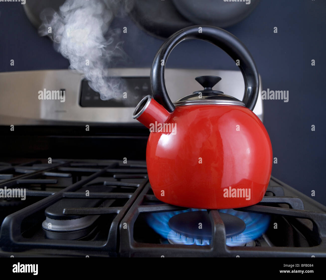 A red teapot is on the boil and steam is pouring out of the spout. - Stock Image