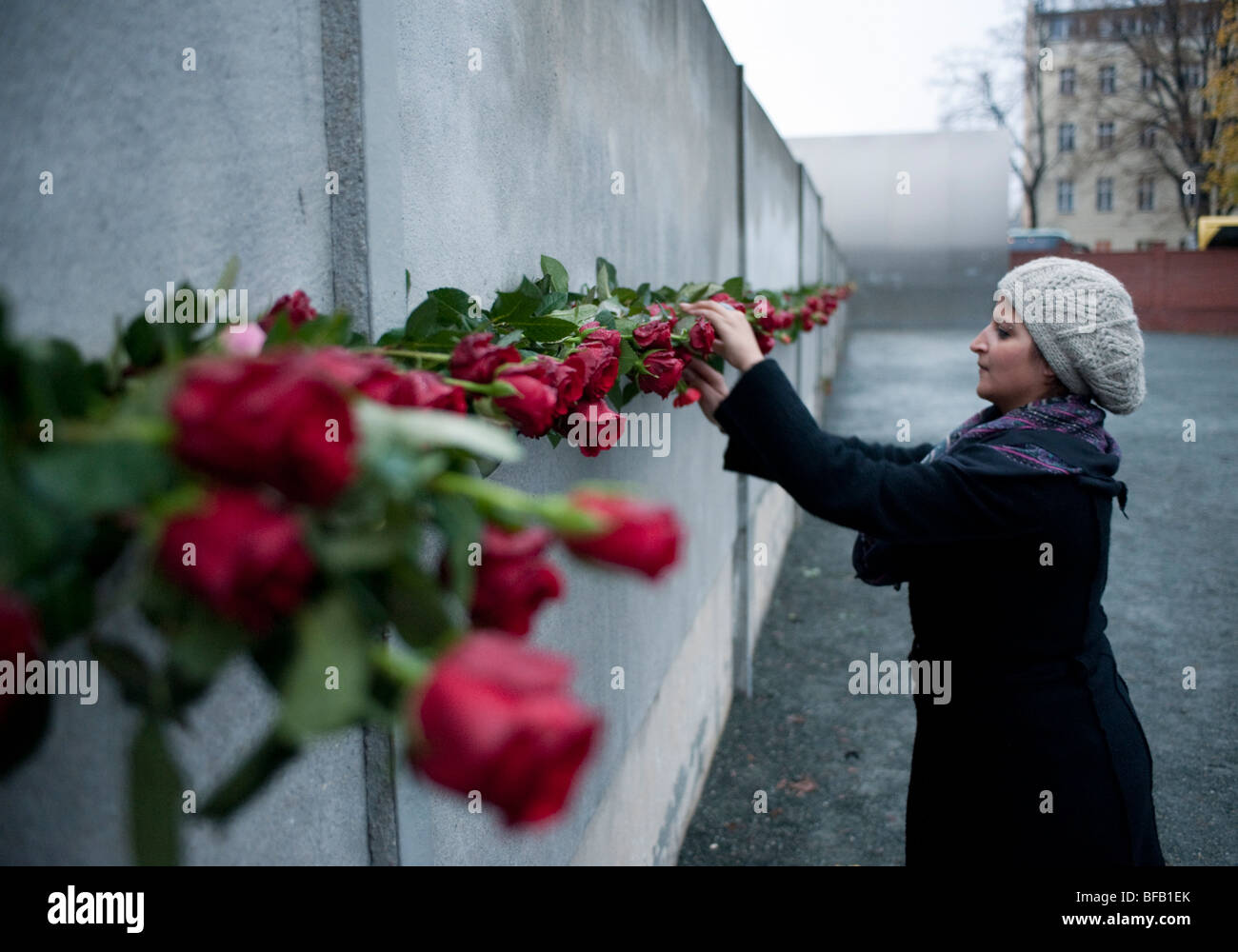 Woman placing red rose in Berlin Wall on 20th anniversary of the fall of the wall to commemorate those who died - Stock Image