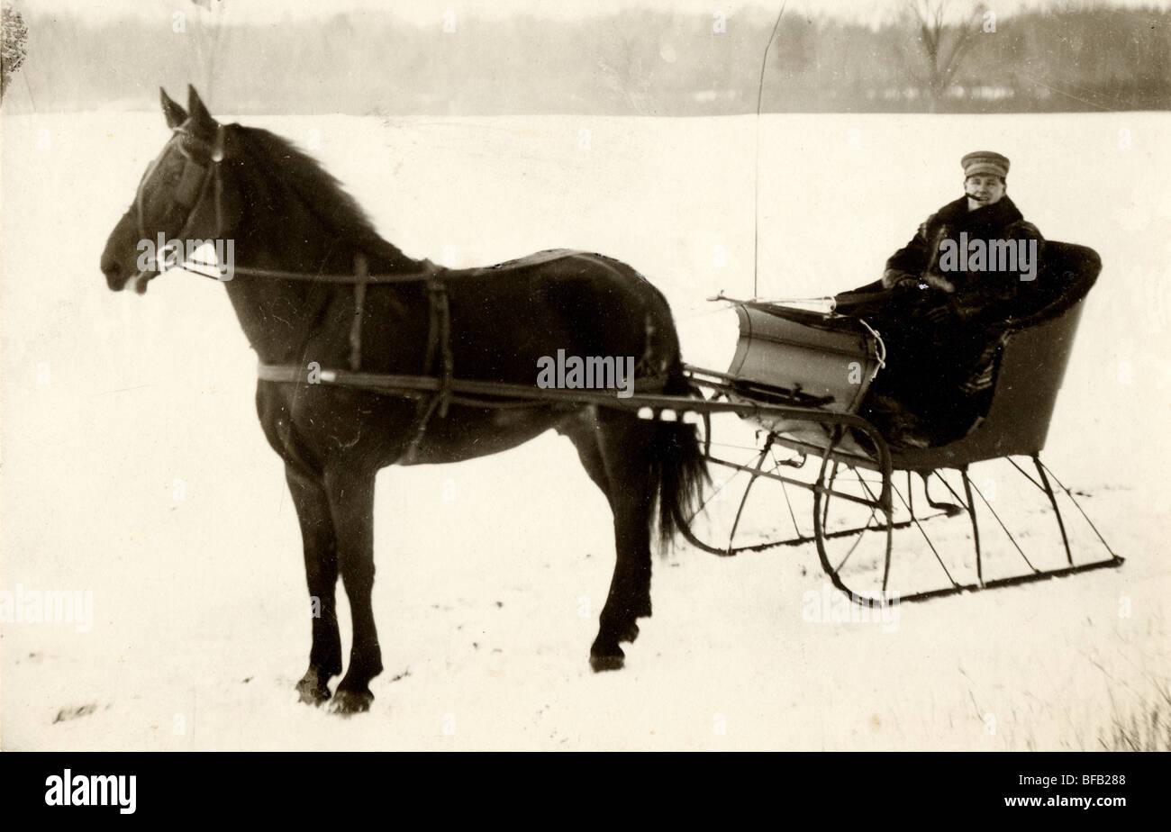 Man Driving Horse Drawn Sleigh at Edge of Frozen Lake Stock Photo