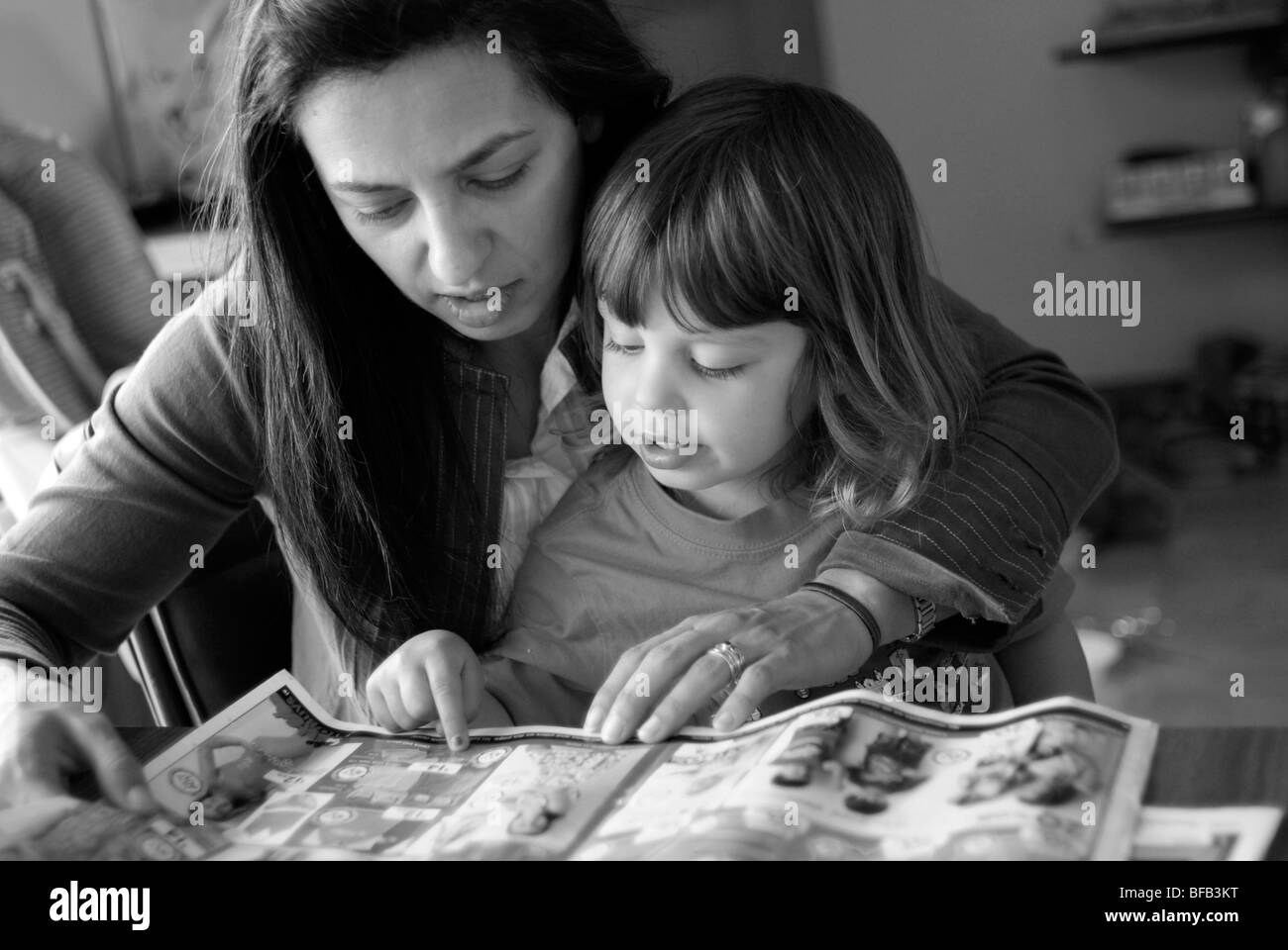 Mother and young daughter, three years old, looking in shopping brochures together. - Stock Image