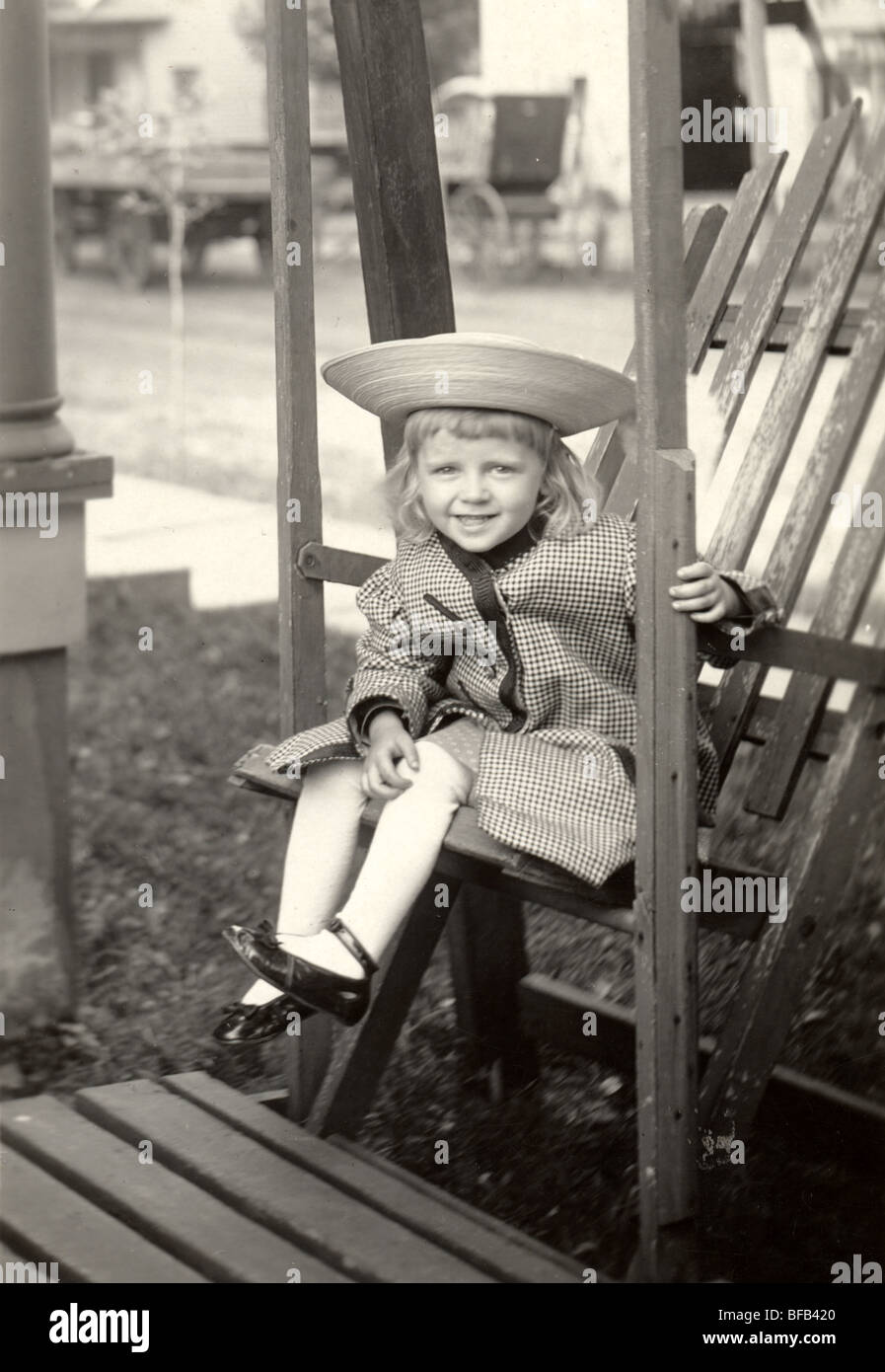 Little Girl in Round Hat Sitting on Swing Set - Stock Image