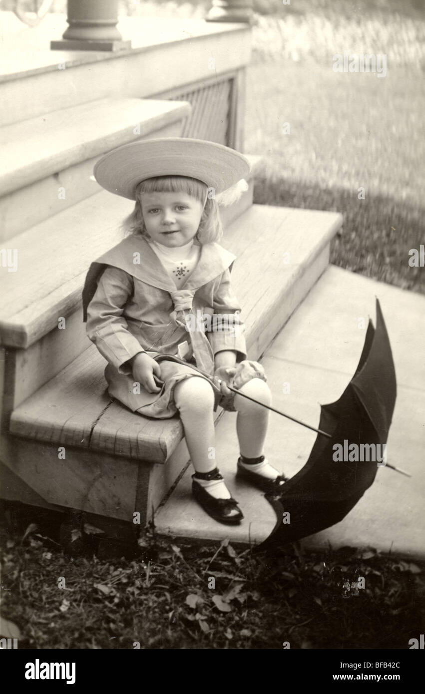 Little Girl with Umbrella Wearing Buster Brown Outfit - Stock Image