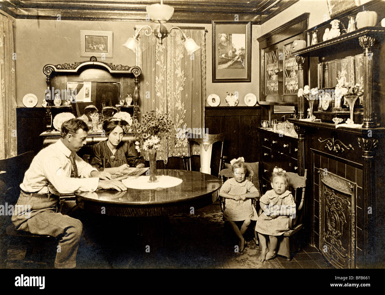 Couple with Twins Looking at Photograph Album - Stock Image