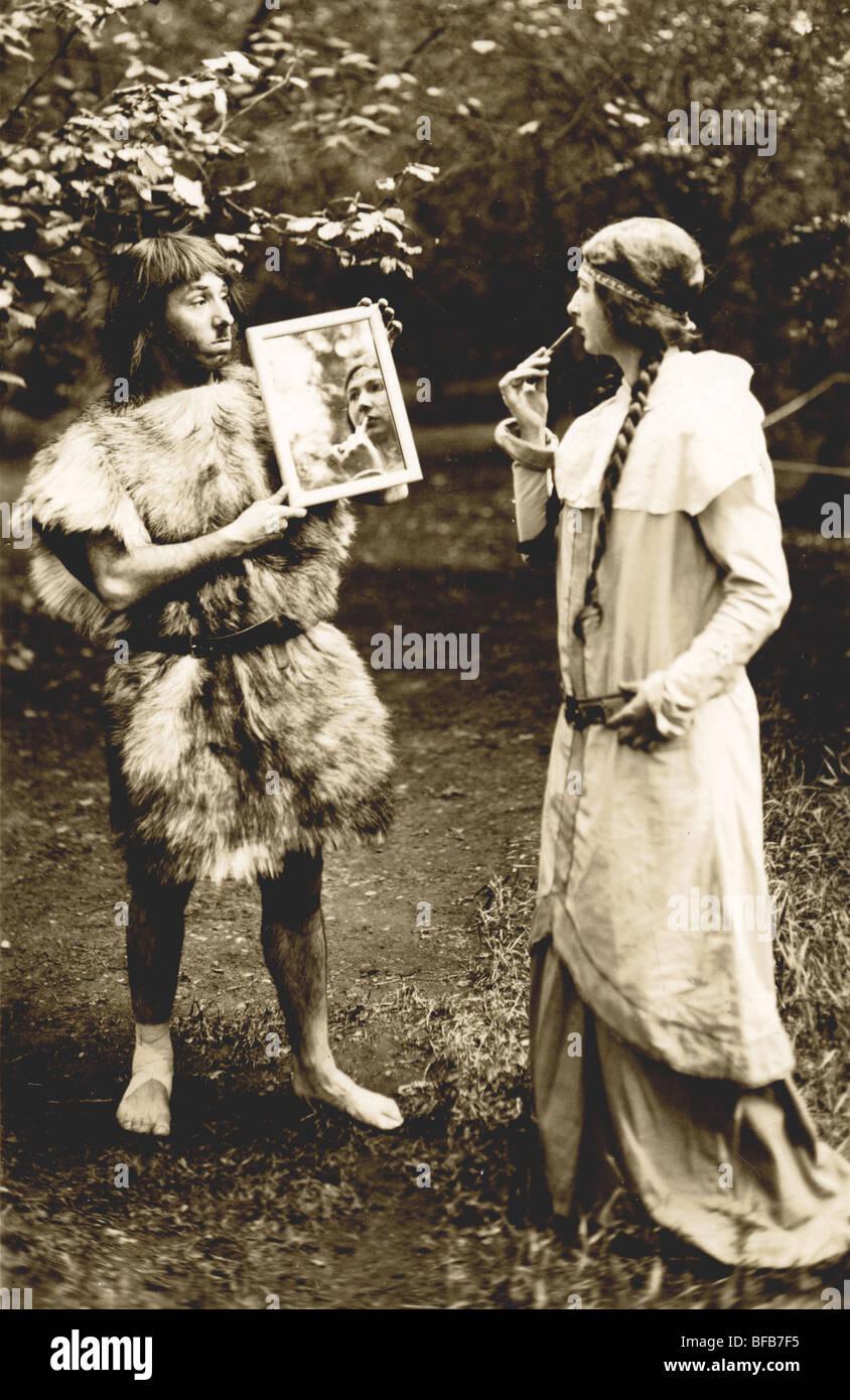 Caveman Holding Up Mirror for Actress Applying Makeup - Stock Image