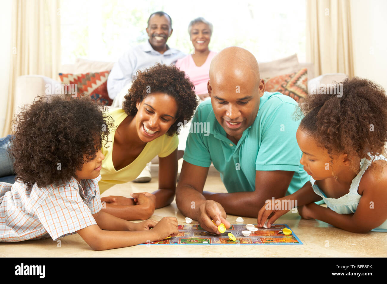 Family Playing Board Game At Home With Grandparents Watching - Stock Image
