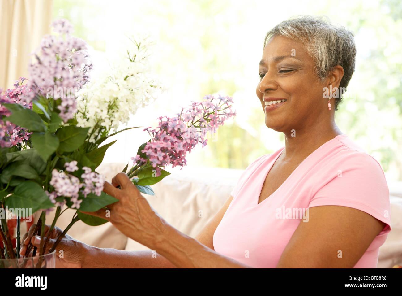 Senior Woman Flower Arranging At Home Stock Photo