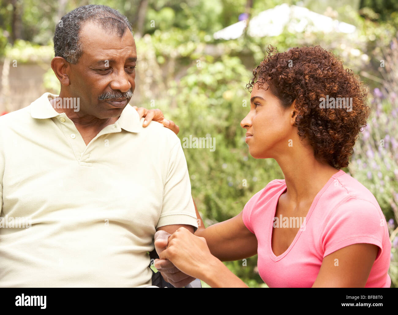 Senior Man Being Consoled By Adult Daughter - Stock Image