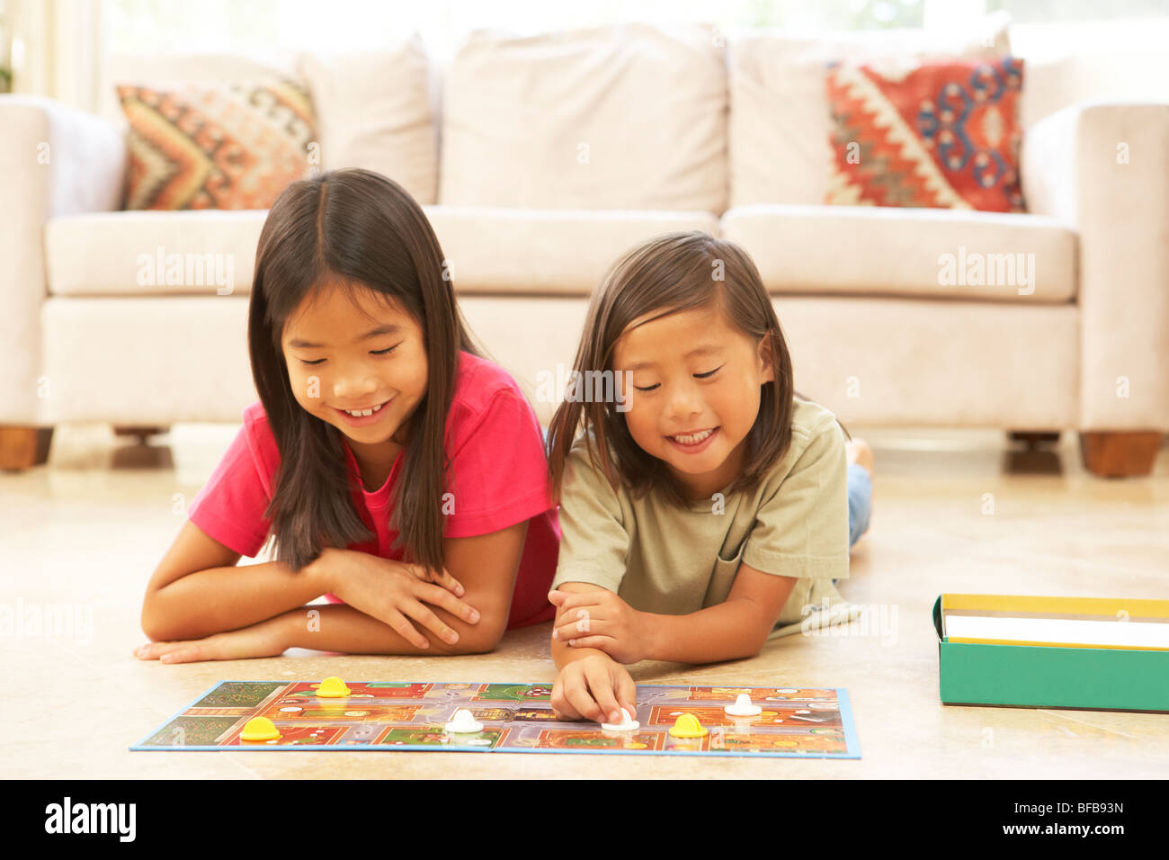 Two Girls Playing Board Game At Home - Stock Image