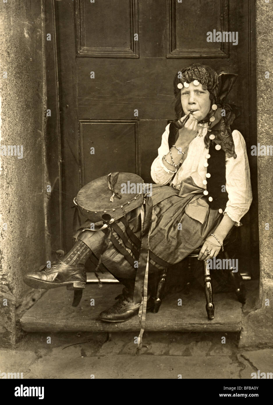 Pipe Smoking Little Gypsy Girl in Doorway - Stock Image