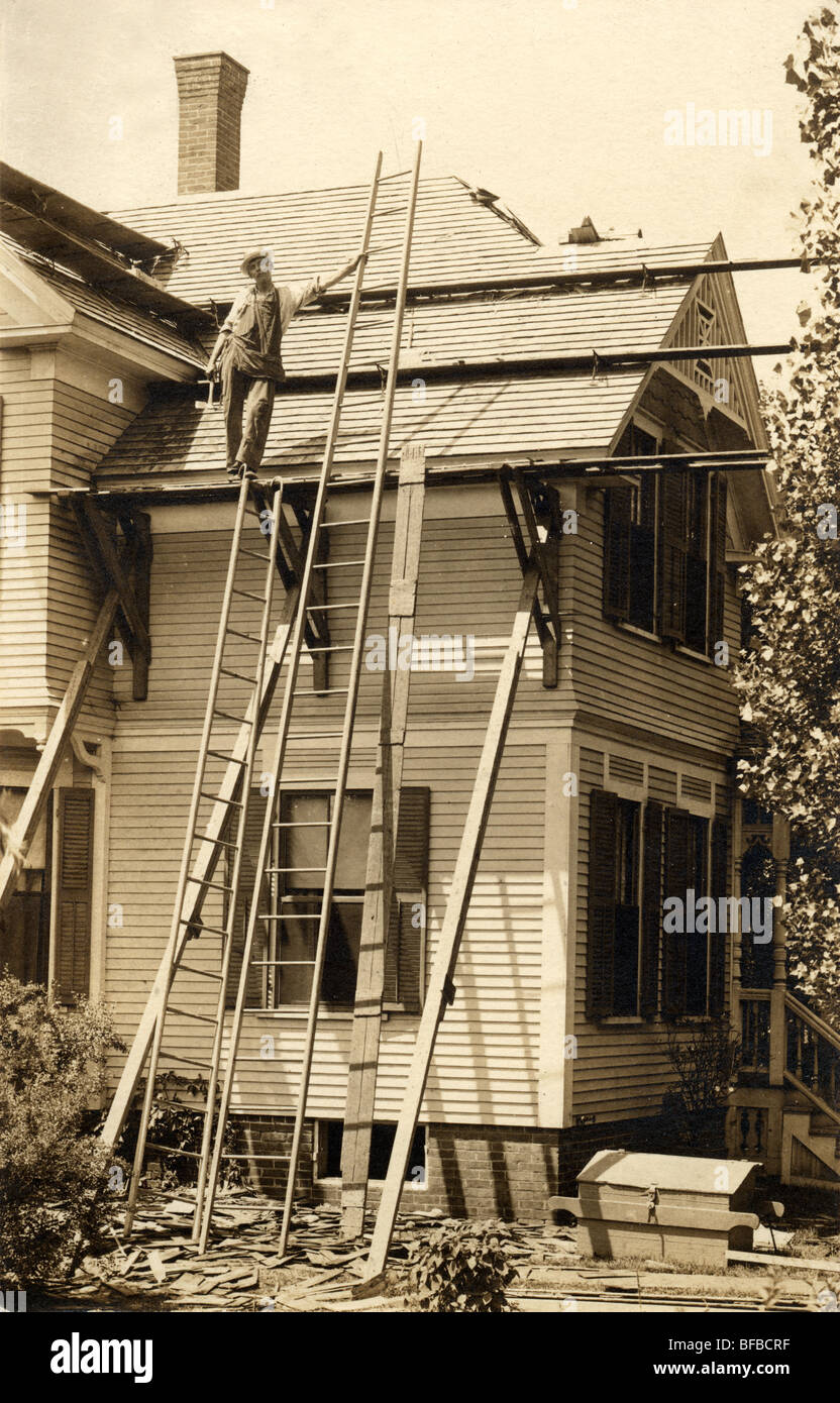 Roofer Repairing Roof on Victorian House - Stock Image